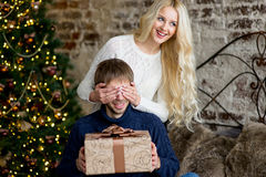 圣诞节夫妇,愉快的年轻女性惊奇人盖子他的眼睛 免版税库存照片