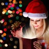 圣诞节奇迹。有圣诞老人帽子开头礼物的愉快的白肤金发的女孩 免版税库存照片
