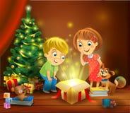 圣诞节奇迹-打开在圣诞树旁边的孩子一件不可思议的礼物 免版税库存图片
