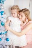 圣诞节女儿她的在结构树附近的母亲 免版税库存照片