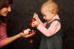 圣诞节女儿她的小母亲发送玩具 免版税库存照片