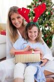 圣诞节女儿礼品打开她的母亲 免版税库存照片