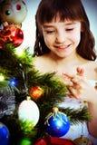 圣诞节女孩少许微笑的结构树下 免版税库存照片