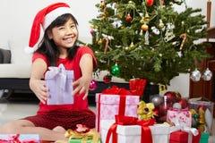 圣诞节女孩指向存在的一点 免版税库存照片