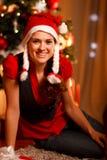 圣诞节女性最近的坐的微笑的结构树 库存图片