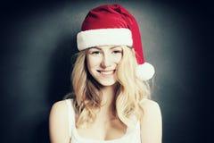 圣诞节妇女笑 在圣诞老人帽子的美好的Xmas时装模特儿 库存照片