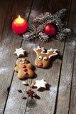 圣诞节姜饼人和驯鹿与蜡烛桂香星瑞士五针松枝杈圣诞节电灯泡在木地板上 免版税库存图片