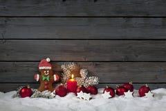 圣诞节姜饼熊圣诞节电灯泡cinnnamon担任主角杉木在堆的枝杈蜡烛雪对木墙壁 免版税库存图片