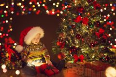 圣诞节婴孩开放当前礼物盒在Xmas树,愉快的孩子下 图库摄影