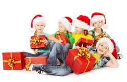 圣诞节孩子在圣诞老人帽子藏品提出红色礼物盒 免版税库存照片
