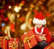 圣诞节孩子打开的当前礼物盒,圣诞老人帽子的愉快的孩子 免版税库存图片