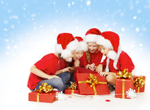 圣诞节孩子打开礼物,在圣诞老人帽子的孩子小组 免版税库存图片