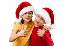 圣诞节定期的女孩和男孩有显示好标志的圣诞老人帽子的 免版税库存照片