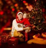 圣诞节家庭乐趣。愉快的拥抱在冷杉tr附近的父亲和孩子 免版税库存照片