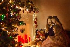圣诞节家庭妇女画象、母亲和女儿当前礼物 免版税库存图片