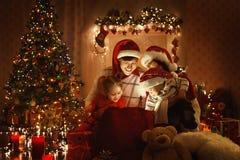 圣诞节家庭开放当前礼物袋子,看对不可思议的光 免版税图库摄影