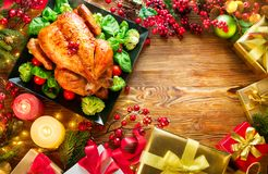 圣诞节家庭晚餐 在假日桌上的烤鸡,装饰用礼物盒、灼烧的蜡烛和诗歌选 免版税库存图片