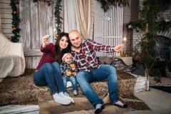 圣诞节家庭画象年轻愉快微笑做父母与拿着闪烁发光物的红色圣诞老人帽子的小孩 寒假Xmas 库存图片