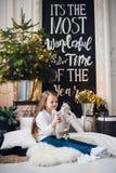 圣诞节家庭装饰 一个小女孩女孩坐在地板上的格子花呢披肩 非常使用与玩具的美丽的女孩在 免版税库存照片