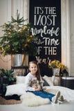圣诞节家庭装饰 一个小女孩女孩坐在地板上的格子花呢披肩 非常使用与玩具的美丽的女孩在 库存图片