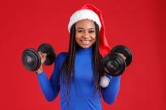 圣诞节帽子、举行哑铃和微笑的一个愉快的非裔美国人的女孩 库存图片