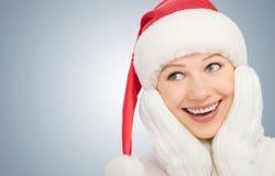 圣诞节帽子和手套的愉快的少妇 库存照片