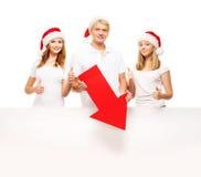 圣诞节帽子的三个愉快的少年指向在横幅的 图库摄影