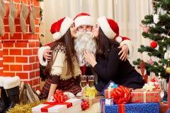 圣诞节帽子的两个女孩亲吻新的y的圣诞老人 库存照片