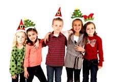 圣诞节帽子的五个逗人喜爱的孩子在胳膊武装 免版税图库摄影