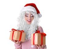 圣诞节帽子的可爱的夫人和伪造品圣诞老人刮胡须拿着礼物盒 免版税库存照片