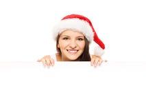 圣诞节帽子的可爱的少年女孩有一个空白的广告牌的 库存照片