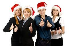 圣诞节帽子的四个年轻人买卖人 库存图片