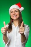 圣诞节帽子的女孩在一个绿色背景 免版税库存照片