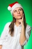 圣诞节帽子的女孩在一个绿色背景 库存图片