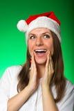 圣诞节帽子的女孩在一个绿色背景 免版税图库摄影
