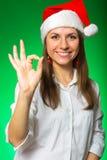 圣诞节帽子的女孩在一个绿色背景 免版税库存图片