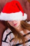 圣诞节帽子的女孩 棕色椅子 库存照片