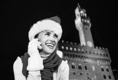 圣诞节帽子的妇女反对Palazzo Vecchio谈话在机动性 免版税库存图片