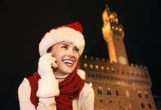 圣诞节帽子的妇女有反对Palazzo Vecchio的机动性的 库存图片