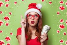 圣诞节帽子的妇女有金钱的 库存照片