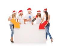 圣诞节帽子的少年指向在一空白的banne的一个小组  免版税库存照片