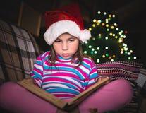圣诞节帽子的惊奇的女孩有书的 免版税库存图片