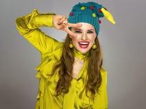 圣诞节帽子的愉快的少妇在灰色背景 免版税库存照片