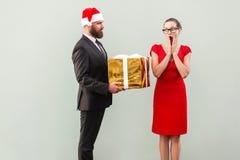 圣诞节帽子的有胡子的人给r的一名当前美丽的妇女 免版税图库摄影