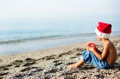 圣诞节帽子的男孩在海旁边 库存图片