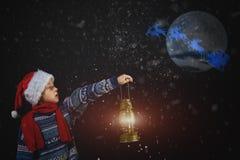 圣诞节帽子的男孩有在手中灯笼的,点在他的雪橇的方式圣诞老人飞行与月亮 库存图片