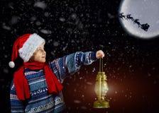 圣诞节帽子的男孩有在手中灯笼的,点在他的雪橇的方式圣诞老人飞行与月亮 免版税库存照片
