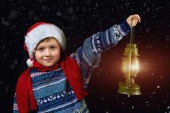 圣诞节帽子的男孩有在手中灯笼的,点在他的雪橇的方式圣诞老人飞行与月亮 库存照片