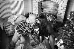 圣诞节年轻愉快的父母家庭画象有小孩子的在圣诞树和壁炉吃附近的红色圣诞老人帽子的 免版税库存图片
