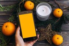 圣诞节广告概念 拿着有空的scr的手电话 免版税库存图片